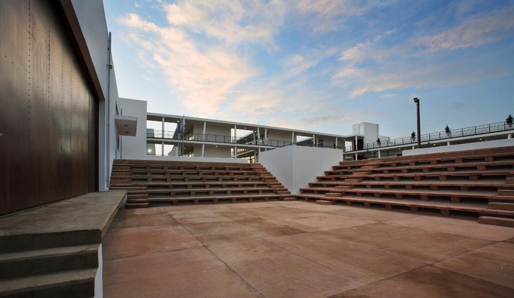 Το υπαίθριο θέατρο ως επέκταση της πλατείας/ κεντρικής αυλής του σχολείου.  Στα αριστερά, η διαμπερής σκηνή της αίθουσας πολλαπλών χρήσεων εξυπηρετεί τόσο εσωτερικά την αίθουσα, όσο και εξωτερικά τις υπαίθριες εκδηλώσεις, © Χρίστος Παπαντωνίου
