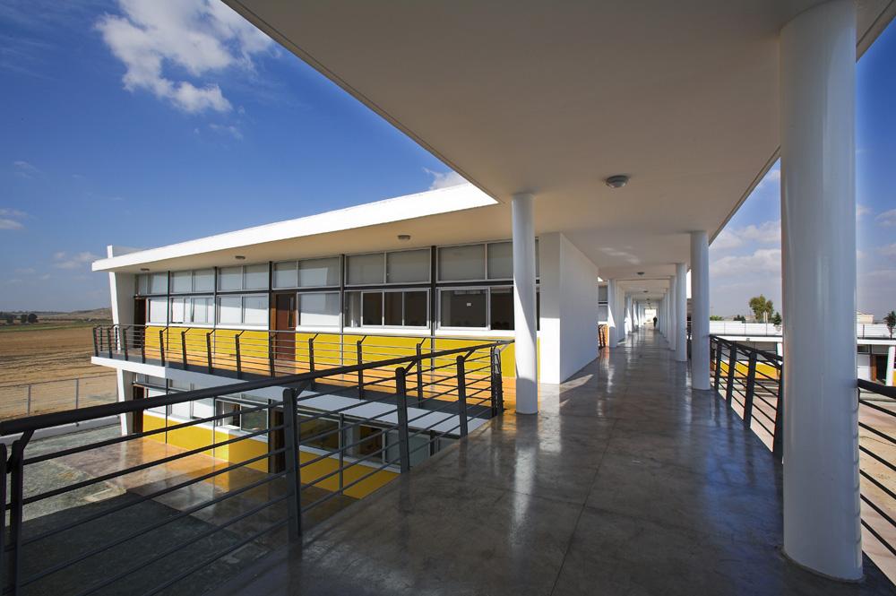 Η στοά με τις αίθουσες διδασκαλίας στραμμένες προς τη μεσημβρία.  Τα μπαλκόνια και οι πρόβολοι εξυπηρετούν ταυτόχρονα λόγους βιοκλιματικούς (σκίαση κατά τους μήνες που ο ήλιος είναι ανεπιθύμητος), © Χρίστος Παπαντωνίου