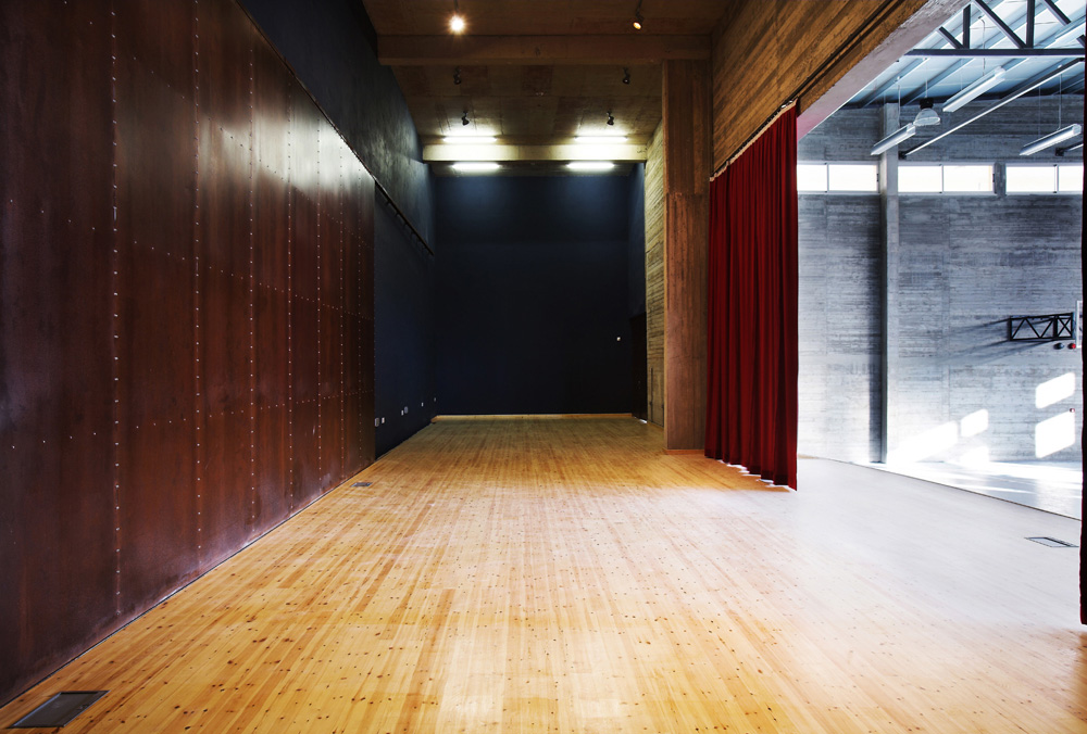 Η σκηνή και τα παρασκήνια της αίθουσας πολλαπλών χρήσεων.  Οι μεγάλες συρόμενες πόρτες στα αριστερά όταν ανοίγουν επιτρέπουν τη χρήση της σκηνής από το υπαίθριο θέατρο, © Χρίστος Παπαντωνίου