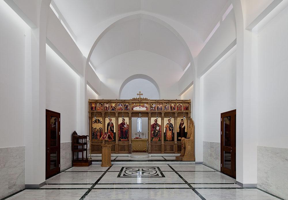 Η εκκλησία από την κύρια είσοδο προς το ιερό βήμα.  Οι πλατιές δοκοί μπροστά από τις ζώνες ανοιγμάτων κάτω από τον θόλο εμποδίζουν το φυσικό φως να μπαίνει απευθείας στον χώρο, ενώ η οριζόντια επιφάνεια της δοκού αντανακλά το φως και ενισχύει τον φωτισμό του θόλου.  Το ίδιο ισχύει και για το ιερό, όπου η κόγχη παραμένει σε απόσταση από τον τοίχο, ώστε να επιτρέπει στο φως να μπαίνει έμμεσα και η ίδια η κόγχη του ιερού να λειτουργεί σαν φωτεινή επιφάνεια, © Creative Photo Room