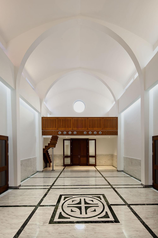 Η εκκλησία από το ιερό βήμα προς την κύρια είσοδο.  Στο δάπεδο χρησιμοποιήθηκαν μεγάλες πλάκες μαρμάρου, ενώ οι χαράξεις υποστηρίζουν και ακολουθούν την όλη συνθετική οργάνωση του χώρου.  Στο βάθος το υπερώο, του οποίου το πάχος του πατώματος αξιοποιήθηκε για εγκατάσταση και απόκρυψη του συστήματος θέρμανσης και δροσισμού, © Creative Photo Room