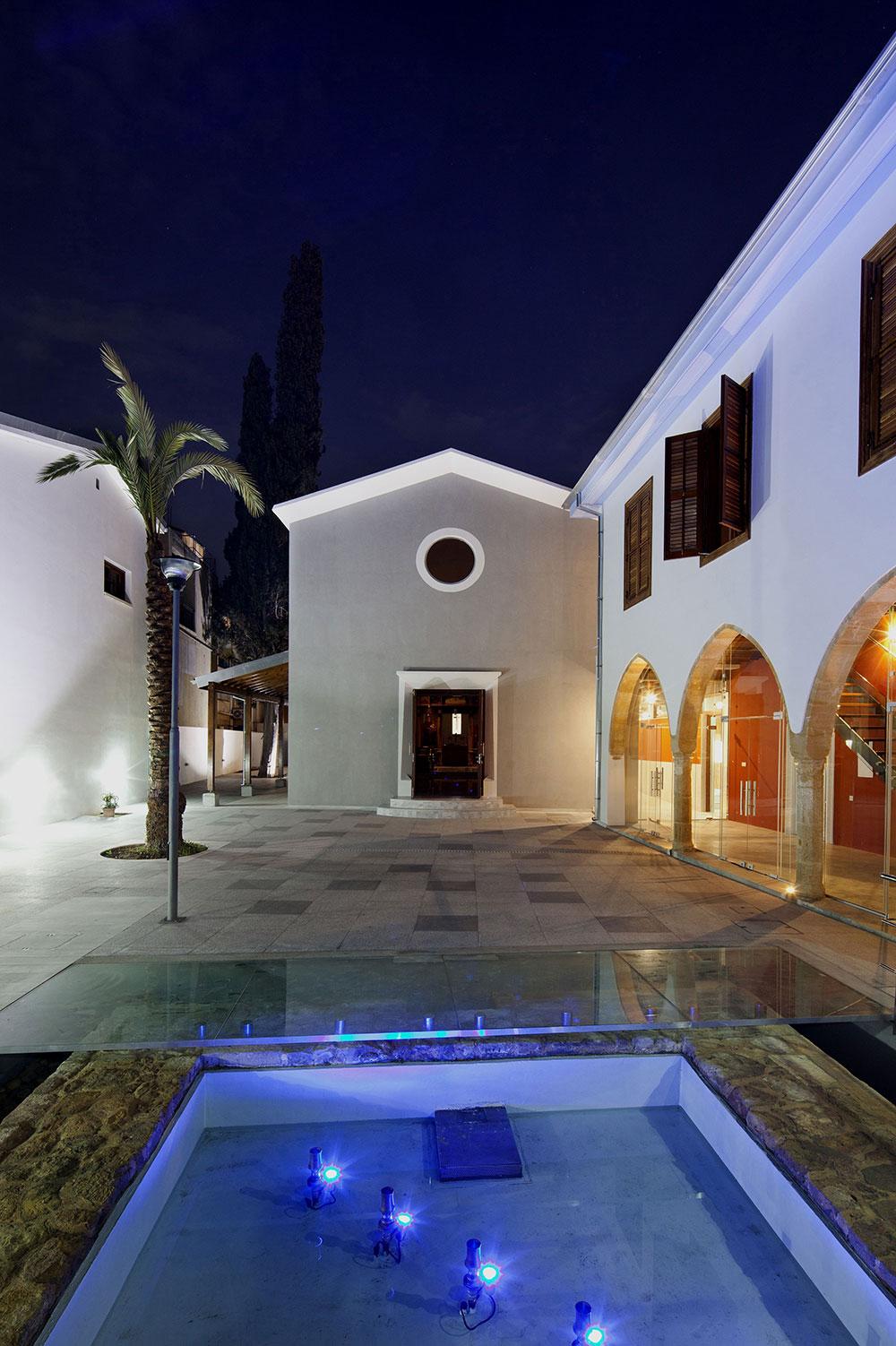Η «επίσημη» αυλή στα νότια, με την εκκλησία στο κέντρο και το υφιστάμενο διατηρητέο στα δεξιά.  Σε πρώτο πλάνο η παλιά δεξαμενή, η οποία συντηρήθηκε και εντάχθηκε στον όλο σχεδιασμό του υπαίθριου χώρου, © Creative Photo Room