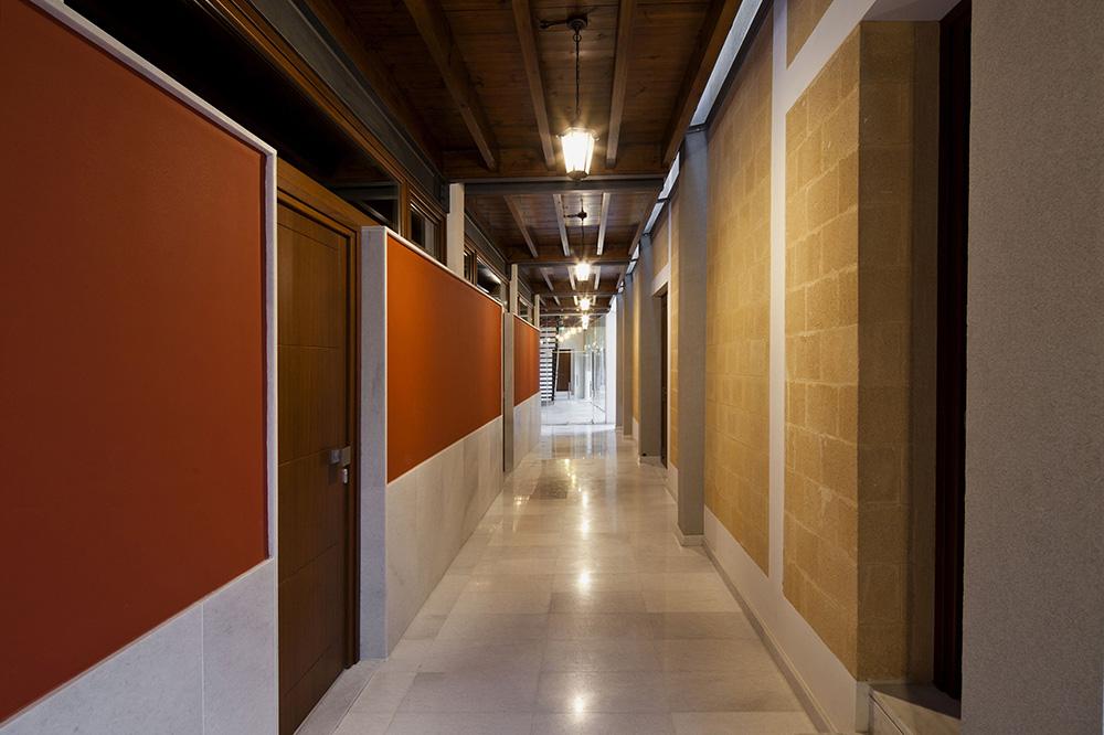 Όλοι οι χώροι επικοινωνούν μεταξύ τους με καλυμμένους, ημιϋπαίθριους διαδρόμους/ στοές, κάτι που, πέραν από την καθαρά λειτουργική και πρακτική σημασία, έχει άμεσες αναφορές στην τυπολογία της μοναστηριακής αρχιτεκτονικής.  Υλικά και χρώματα παραπέμπουν στην παράδοση, μέσα όμως από μια εντελώς σύγχρονη αρχιτεκτονική γλώσσα, αποφεύγοντας την αντιγραφή και τη μίμηση, © Creative Photo Room
