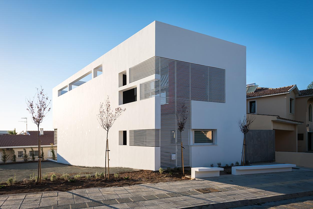Άποψη κατοικίας από ΝΑ. Ο όγκος του κτιρίου με τις διαφορετικές ποιότητες ανοιγμάτων (κενά, ημιδιαφανή, διαφανή) που συμβάλλουν στην έντονη διαφοροποίησή του την ημέρα και τη νύχτα, © Χάρης Σολωμού (Architectural Photography)