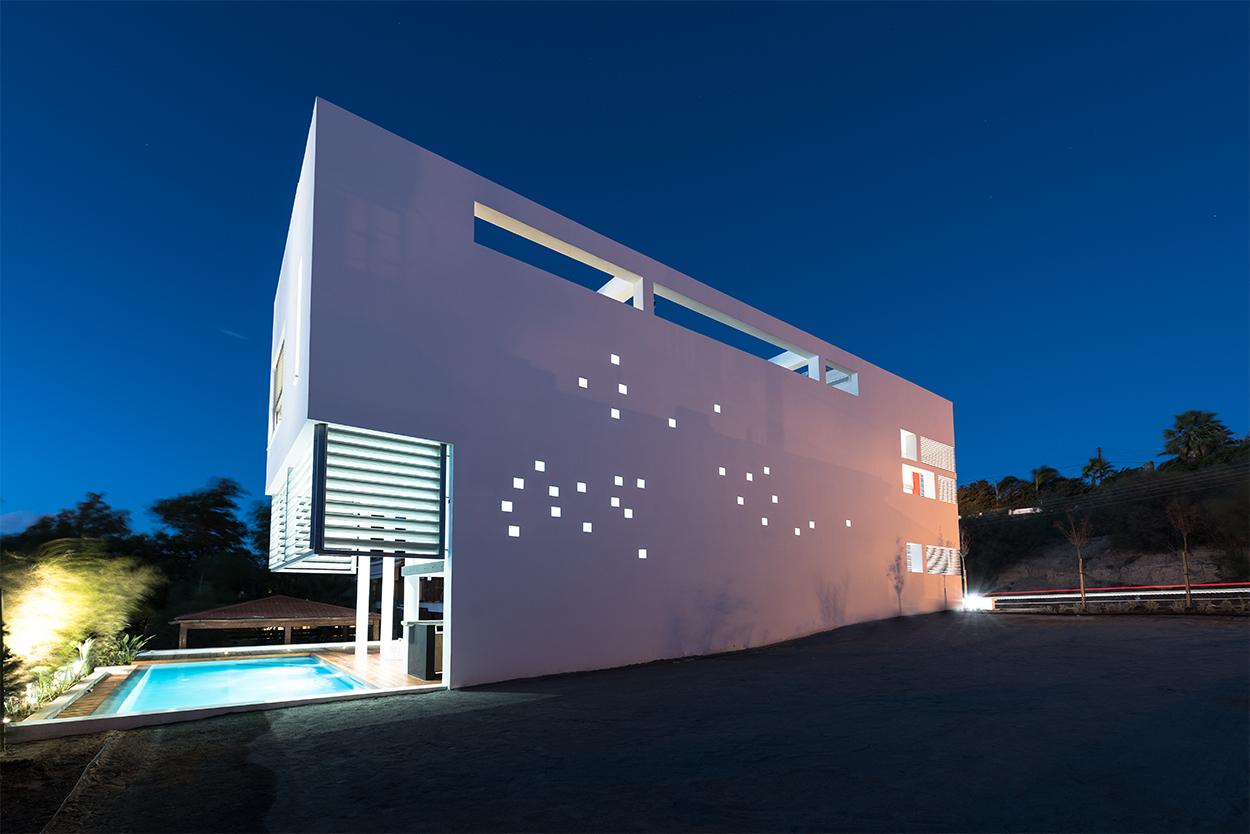 Νυχτερινή άποψη κατοικίας από τα νότια. Η «τυφλή» όψη αντιμετωπίζεται ως μια από τις όψεις του κτιρίου, με την υποχώρηση των βασικών χώρων και την «πλαστική» αντιμετώπισή της (δοκίδες, ανοίγματα, υαλότουβλα) , © Χάρης Σολωμού (Architectural Photography)