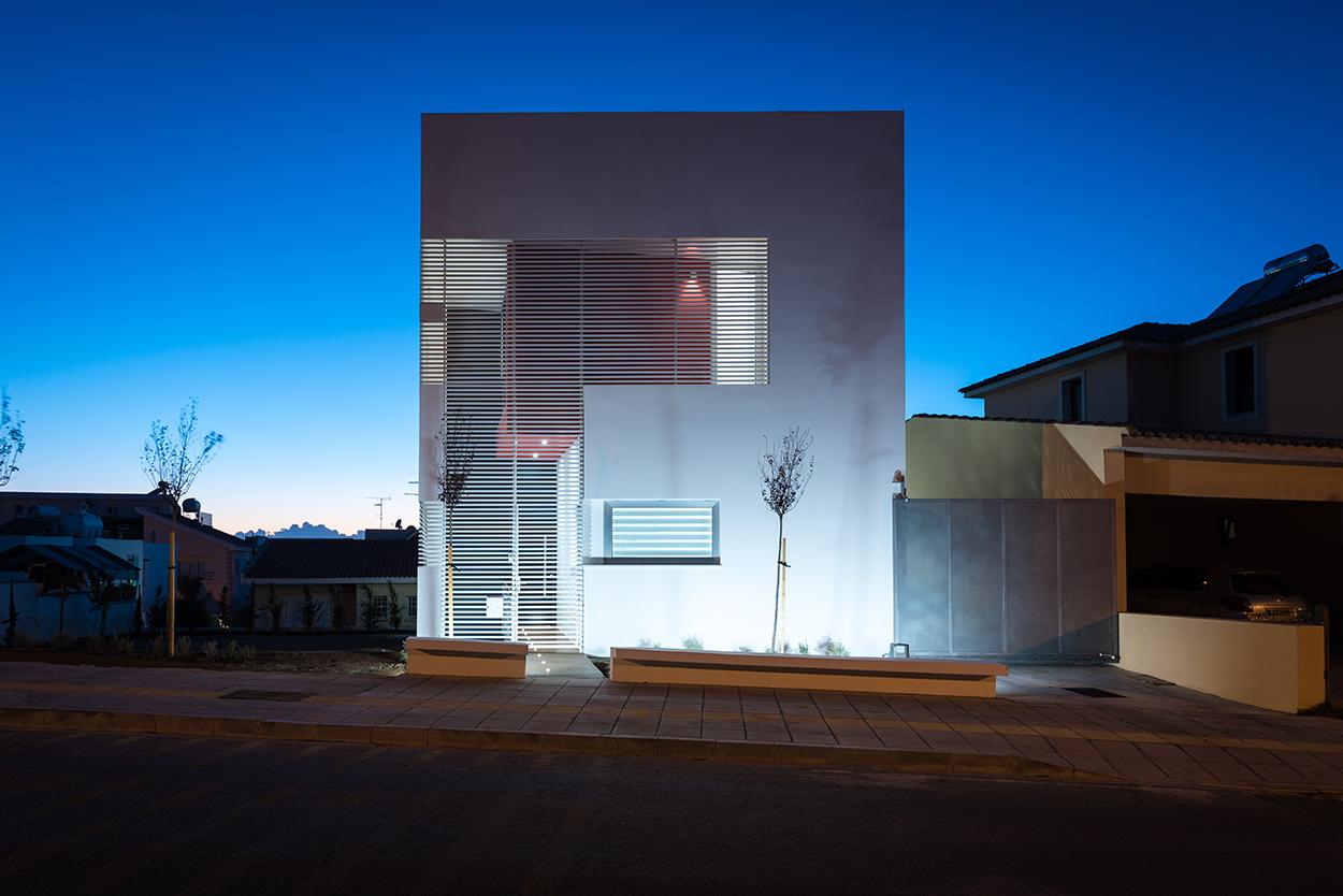 Νυχτερινή άποψη της πρόσοψης (ανατολικής όψης) της κατοικίας. Οι λεπτές δοκίδες αλουμινίου λειτουργούν ως φίλτρα, συμβάλλοντας και καθορίζοντας την αισθητική ταυτότητα του κτιρίου, © Χάρης Σολωμού (Architectural Photography)
